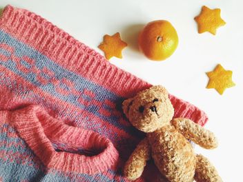 Children's sweater and a toy bear, tangerines on a white background - бесплатный image #198783