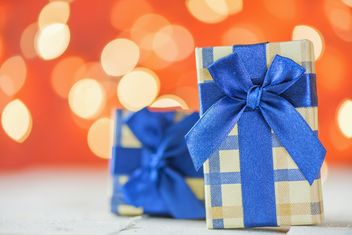 Small presents with blue ribbons on red blur background - image gratuit #271603