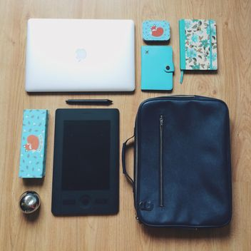 Macbook, wacom tablet, blue notebooks and black bag on wooden background - Kostenloses image #271733
