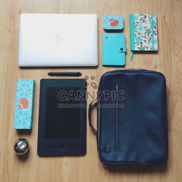 Macbook, wacom tablet, blue notebooks and black bag on wooden background - Free image #271733