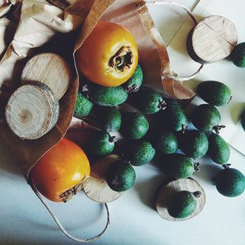 Feijoa and persimmons scattered from a paper package - бесплатный image #272193