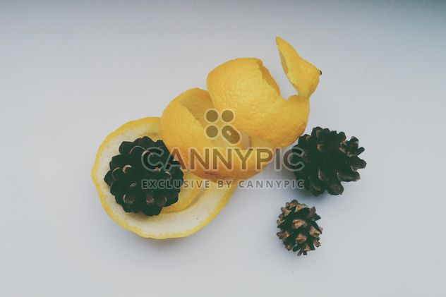 Lemon peel and pine cones over white background - Free image #272213