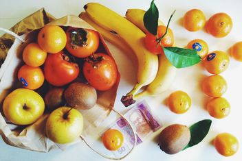 bananas, tangerines, kiwis, apples and persimmons in bag on white background - image #272273 gratis