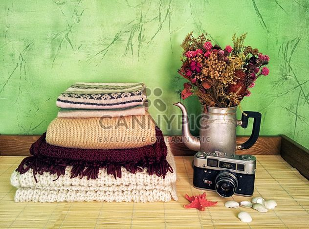 Warm clothes, retro camera and flowers in old teapot on the table - Free image #272303