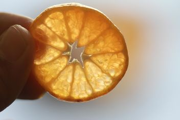 Orange slice in a hand - image #301943 gratis