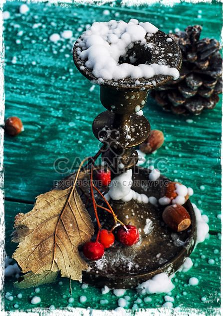 Candlestick, rowan berries, hazelnuts and dry leaf in snow on green wooden background - Free image #302033