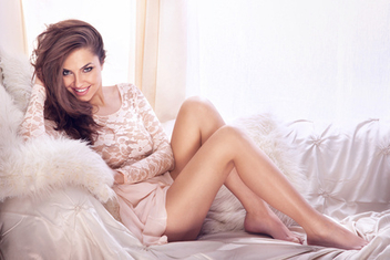 Young beautiful smiling woman relaxing on white couch. - бесплатный image #315383