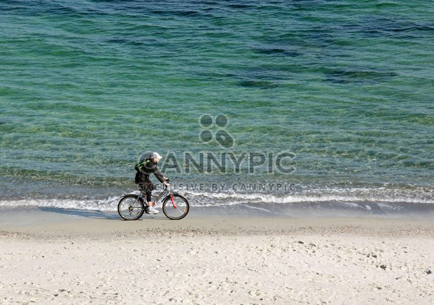 Woman riding a bicycle down the beach - image gratuit #330323
