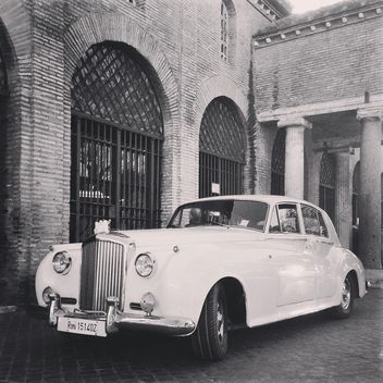 White Bentley near old brick building, black and white - image gratuit #331833