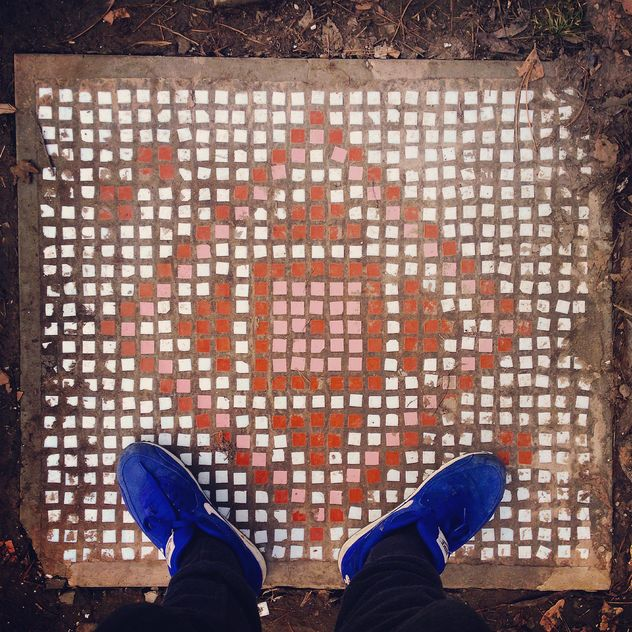 Feet in blue sneakers on pavement slab - image gratuit #332073