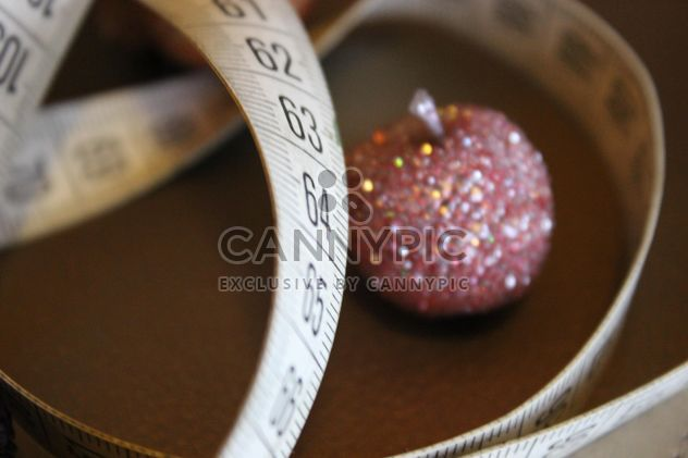 Still life of white measure tape with pink glitter toys - Free image #341453