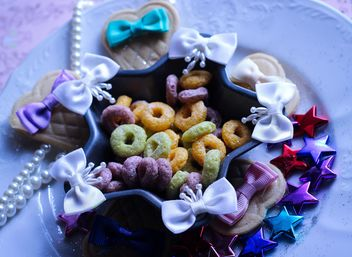 Decorative bows, tinsel and candies on the plate - бесплатный image #342073