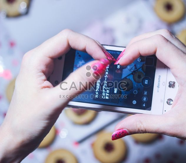 Smartphone decorated with tinsel in woman hands - Free image #342173