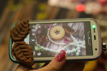 Smartphone decorated with tinsel in woman hands - image gratuit #342183