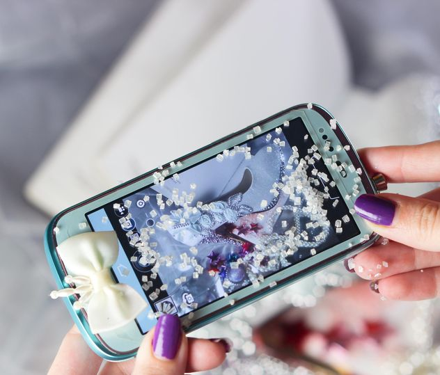 Smartphone decorated with tinsel in woman hands - бесплатный image #342193