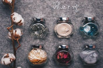 Small jars with decorations and branch of cotton on background - бесплатный image #342543