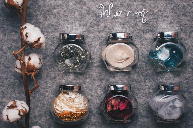 Small jars with decorations and branch of cotton on background - Kostenloses image #342543