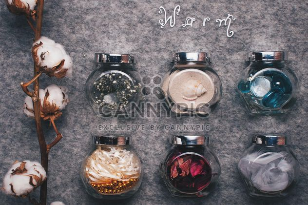 Small jars with decorations and branch of cotton on background - Free image #342543