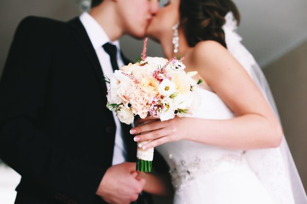 Happy wedding couple kissing - image #345883 gratis