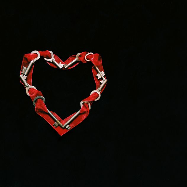 Heart made of keys and ribbons on black background - image #345913 gratis