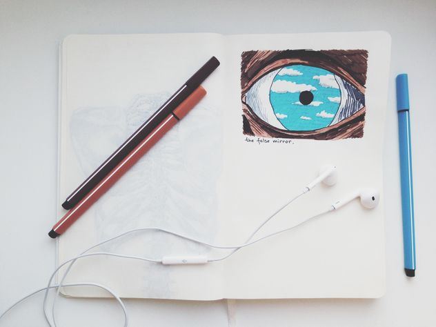 Earphones and markers on notebook with picture - Free image #346563