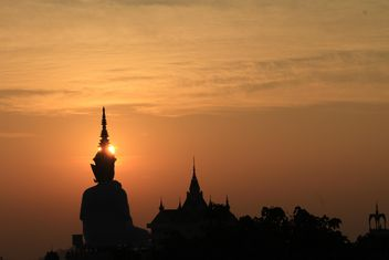 Silhouette of Buddha statue and temple at sunset - Free image #346573