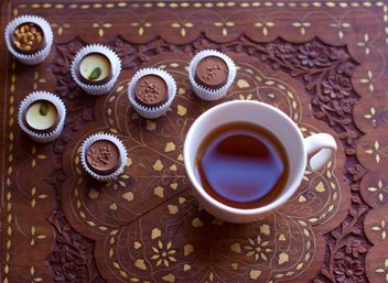 Cup of hot tea and candies on wooden background - бесплатный image #347913