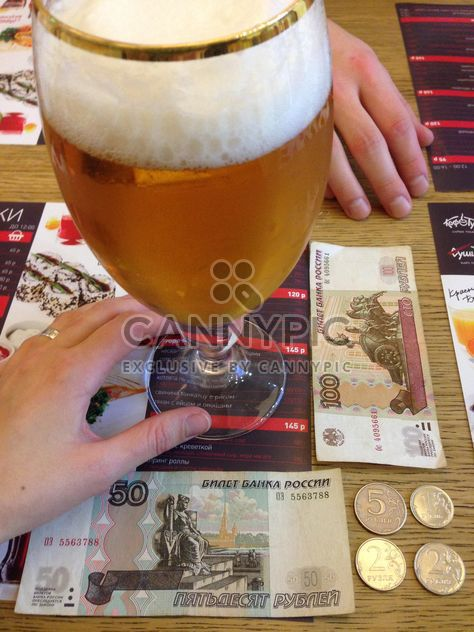 Glass of beer and money on table in cafe - Free image #347933