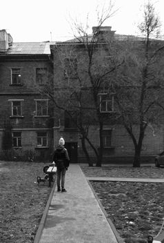 Person in front of house in town, black and white - бесплатный image #348033