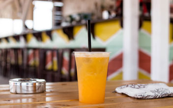 Orange drink in plastic cups with ice on the beach. - Free image #447523