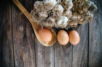 Garlic, eggs and wooden spoon on dark wooden background - бесплатный image #452403