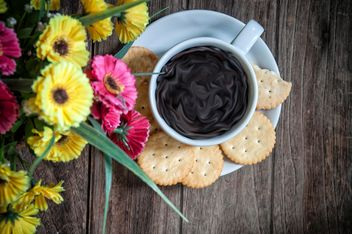 Cookies, cup of coffee and flowers on wooden background - бесплатный image #452413