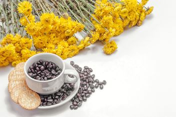 Cookies, cup of coffee beans and flowers over white background - Free image #452433