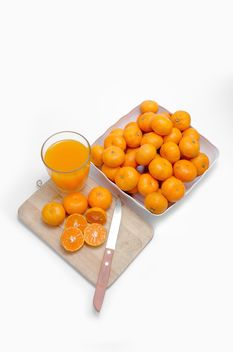 Oranges on the desk with knife and glass of juice on white background - Free image #452523