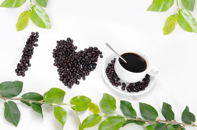 cup of coffee,coffee beans laid out in the shape of heart and green leaf on white background - image #452573 gratis