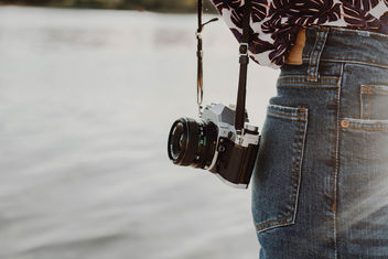 Lifestyle photo of a vintage film camera on a girl. Sea background.jpg - image #454473 gratis