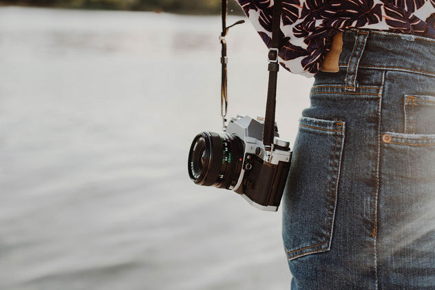 Lifestyle photo of a vintage film camera on a girl. Sea background.jpg - image gratuit #454473