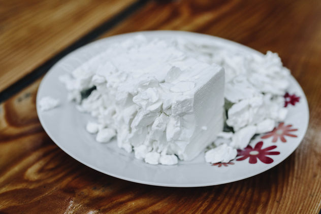 Feta cheese in a white plate on wooden background - бесплатный image #454873