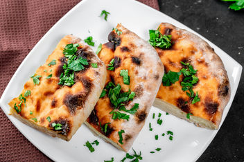 Sliced traditional cheese khachapuri on a plate with greens - Free image #459683