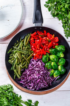 Frying pan with Brussels sprouts, pepper, asparagus and red cabbage. Top view - Free image #459703