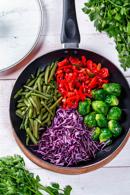 Frying pan with Brussels sprouts, pepper, asparagus and red cabbage. Top view - бесплатный image #459703